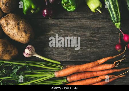 Gemüse auf Holz Hintergrund, Rahmen Komposition. Kartoffeln, Karotten, Knoblauch, Paprika, Zucchini und Radieschen auf alten Holztisch, kopieren Platz für Text. Ag - Stockfoto