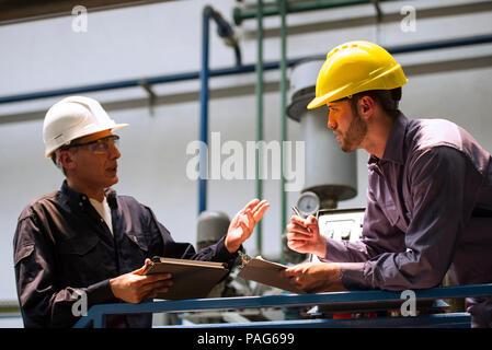 Fabrikarbeiter diskutieren miteinander in der Factory - Stockfoto