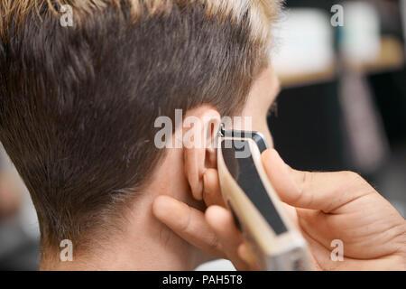 Barbier hand mit Haarschneider, neuer Haarschnitt für Client vor dem Spiegel zu sitzen. Modell in dunklen, getönten Haare, freuen. Arbeiten in modernen spacigen Friseur, Beauty Salon. - Stockfoto