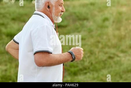 7/8-Foto von alter Mann hören von Musik während der Ausführung. Modell tragen weiße Poloshirt mit dunkelblauen Streifen, Sportuhr, rot Kopfhörer. Exercesing im City Park auf grünem Gras Hintergrund. - Stockfoto