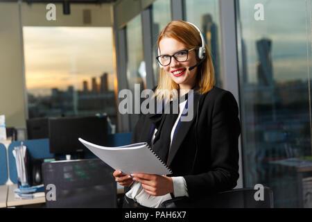 Fotos von lächelnden Frau mit Brille und Kopfhörer mit Papier in den Händen in der Nähe von Glas Wand - Stockfoto