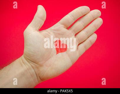 Liebe in die Hände eines Mannes mit vielen Gefühlen und Emotionen aus einer Beziehung von einem Herzen auf einem Palm auf einem roten Hintergrund dargestellt vorgeschlagen - Stockfoto