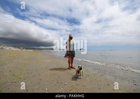 Langer Rock, Cornwall, UK. 24. Juli 2018. UK Wetter. Die far south west Cornwall hatte Regen über Nacht. Die Mittagszeit war noch warm, wie Leute ihre Hunde am Strand in der Nähe von Marazion ging, Aber dunkle Wolken drohen mehr Regen. Foto: Simon Maycock/Alamy leben Nachrichten - Stockfoto