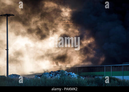 Rostock, Deutschland. 24. Juli, 2018. Dicke Rauchwolken steigen aus einem recyclinghof bei einem Brand. Nach Angaben einer Polizeisprecherin, Anfangs gab es keine Verletzten. Credit: Frank Hormann/dpa/Alamy leben Nachrichten - Stockfoto