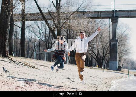 Glückliches Paar in Liebe umarmen und die gemeinsame Nutzung von Emotionen, Hände halten am Ufer des Flusses - Stockfoto