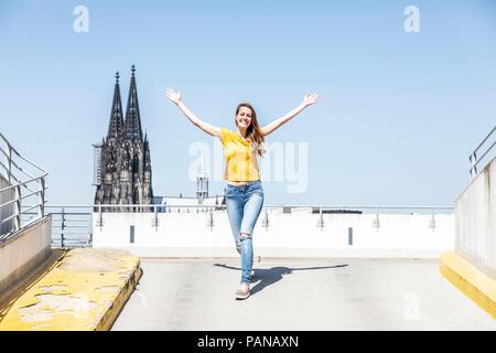 Deutschland, Köln, glückliche Frau auf der Rampe der Parkdeck mit dem Kölner Dom im Hintergrund - Stockfoto