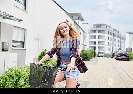 Glückliche junge Frau Reiten Fahrrad im Bereich - Stockfoto