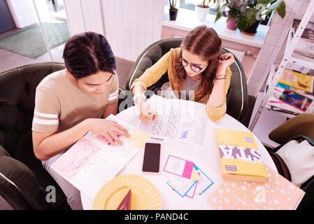 Junge moderne Smart Studenten in kleinen gemütlichen Cafe arbeiten - Stockfoto