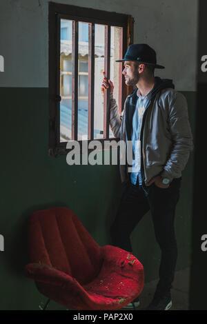 Der bärtige Mann mit schwarzem Hut, schauen aus dem Fenster - Stockfoto