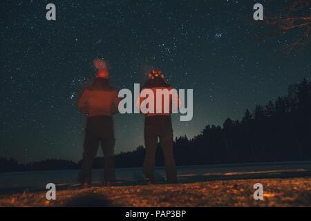 Schweden, Sodermanland, zwei Männer am Lakeside stehen unter Sternenhimmel bei Nacht - Stockfoto