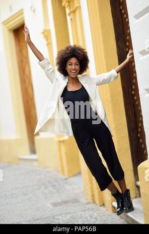 Spanien, Cadiz, Portrait von modische junge Frau mit lockigem Haar vor dem Haus - Stockfoto
