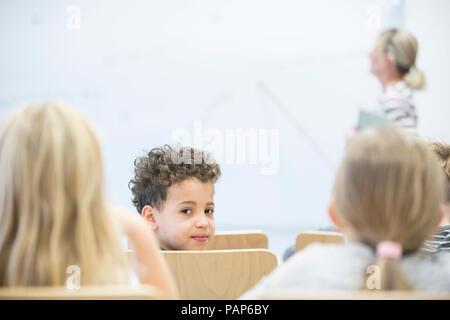 Portrait von Schüler mit Klassenkameraden und Lehrer in der Klasse