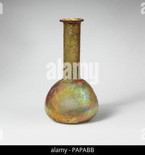 Glas Parfüm Flasche. Kultur: Roman. Abmessungen: Insgesamt: 4 3/4 in. (12,1 cm) Durchm.: 2 1/2 x 1 1/8 in. (6,4 x 2,9 cm). Datum: 2.-3.Jh. N.CHR.. Farblos mit blau-grüne Färbung. Rim ausgeklappt, über, in, auf und in den Seiten der Mund abgeflacht; zylindrische Hals, verjüngt sich nach unten; bauchigen Körper, nach unten erweitert; flachen Boden. Brokwn auf Körper mit einem großen Loch in der Seite; Blasen und blasen Streifen; tiefe Rillen und brillante Schillern, mit kleinen Flecken von dicken, cremigen Verwitterung. Museum: Metropolitan Museum of Art, New York, USA. - Stockfoto