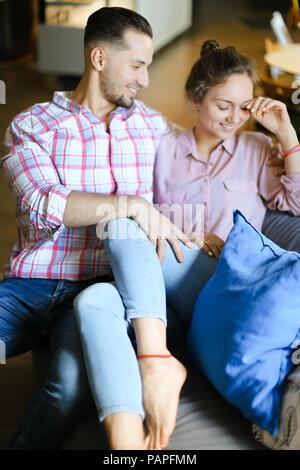 Junge schöne Mädchen sitzen mit Freund innen und sprechen. - Stockfoto