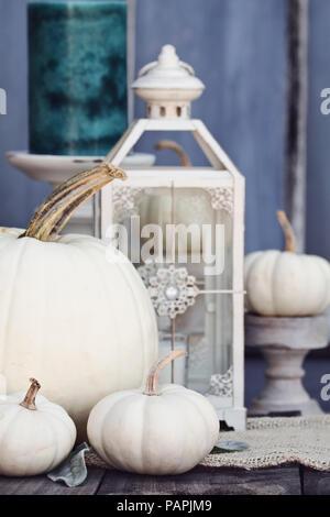 Herbst Dekorationen mit Erbstück mini und großen weißen Kürbisse und Kerzen gegen eine rustikale Herbst Hintergrund. Thanksgiving oder Halloween Dekoration. - Stockfoto