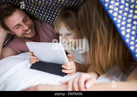 Eltern sahen etwas auf digital Tablet mit ihrer Tochter unter Decke im Bett - Stockfoto