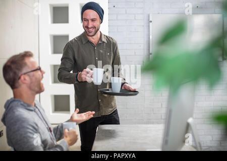 Zwei Kollegen in Kaffeepause am Schreibtisch im Büro - Stockfoto