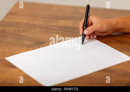 Die hand Schrift auf weißen Blatt auf einer hölzernen Tisch. Die Unterzeichnung des Vertrags. - Stockfoto