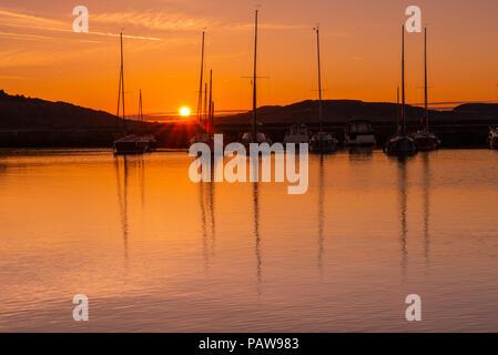 Lyme Regis, Dorset, Großbritannien. Juli 2018. UK Wetter: Golden Sonnenaufgang in Lyme Regis. Die Boote im Hafen sind an einem weiteren heißen und sonnigen Tag im Küstenort Lyme Regis gegen den goldenen Schein des frühen Morgenhimmels silhouettiert. Quelle: DWR/Alamy Live News. - Stockfoto