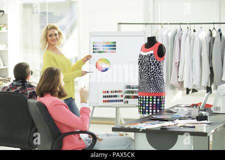 Frau zeigt bei Swatch Farbpalette beim Besprechen welche Farbe mit Kollegen zu wählen - Stockfoto