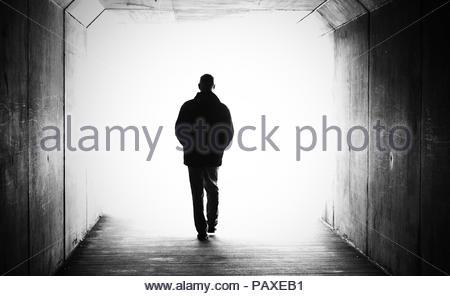 Single silhouetted Abbildung zu Fuß in Richtung ein helles Licht in einen dunklen Tunnel. Tod sterben über Weitergabe Konzept - Stockfoto