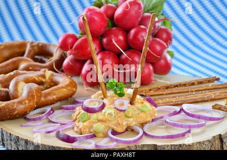 """Bayerische Käsespezialität """"obazda"""", serviert mit Zwiebelringen, Brezeln und Radieschen auf einem hölzernen Platte - Stockfoto"""