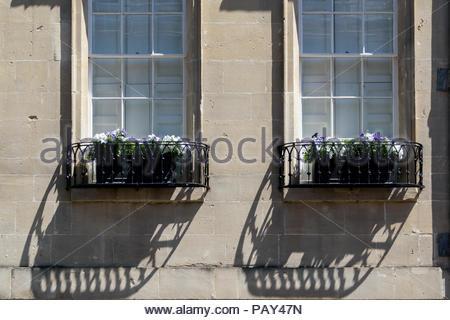 Bild von zwei große Schiebefenster mit ausgefallenen Metall Blumenkästen wirft einen Schatten auf die Gebäude Mauerwerk, Badewanne, Somerset, England, Großbritannien - Stockfoto