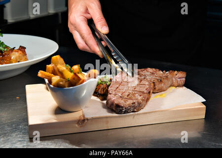 Küchenchef bereitet ein Sirloin Steak für einen seiner Gäste im Restaurant Perla Blanca in Peniscola nördlichen Spanien - Stockfoto