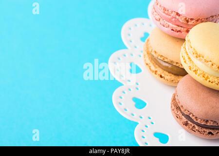 Vielzahl von bunten Rosa Grün Gelb Braun Mokka Kaffee Makronen gestapelt auf Weiße Spitze Kuchen auf Türkisfarbenem Hintergrund abheben. Backwaren Süßwaren - Stockfoto