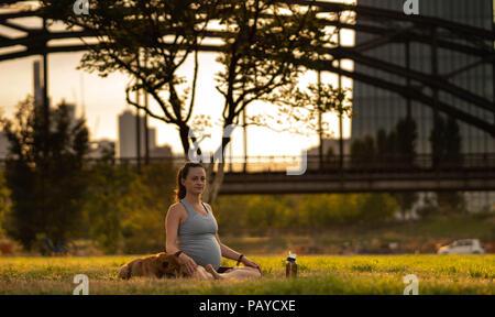 Schöne schwangere junge Frau mit kleinen Hund sitzen auf Matten, Yoga, Entspannung, Gefühl, lebendig, frische Luft, Ruhe und Träumen, im grünen Park. - Stockfoto