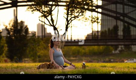 Schöne schwangere junge Frau mit kleinen Hund sitzen auf Matten, Yoga, Entspannung, Gefühl, lebendig, frische Luft, Ruhe und Träumen, im grünen Park. Auf dem Hintergrund der Eisenbahnbrücke und der Stadt - Stockfoto