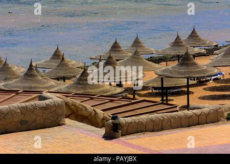Eine Reihe von Stroh Sonnenschirme gegen Überhitzung und Sonnenliegen am Strand vor einem blauen Himmel und das blaue Meer zu schützen. Das Konzept der Sommerferien, - Stockfoto