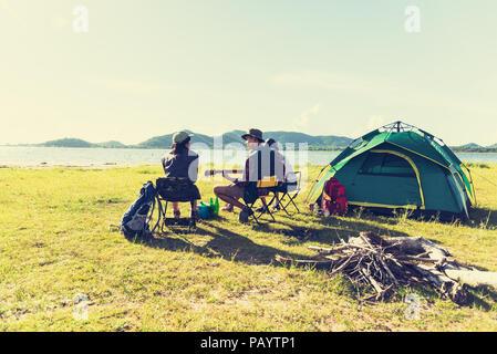 Gruppe von Reisenden, Camping, Picknick und spielen Musik zusammen. Die Berge und den See im Hintergrund. People und Lifestyle. Aktivität im Freien und leis - Stockfoto