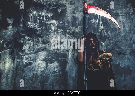 Daemon Hexe mit reaper auf grunge Wand Hintergrund. Halloween und religiöses Konzept. Daemon Engel und Satan Thema. - Stockfoto