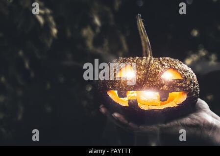 Halloween Kürbis in der Hand, Urlaub und Religion Konzept. Ghost in Kürbis Thema. Hexerei und Mystery buchstabiere Thema. - Stockfoto