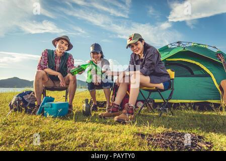 Gruppe von Reisenden, Camping, Picknick in der Wiese mit Zelt im Vordergrund. Die Berge und den See im Hintergrund. Die Menschen und Lebensstile Konzept. Im freien Acti - Stockfoto