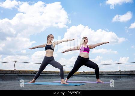 Zwei junge Frauen, die Yoga, Krieger darstellen - Stockfoto