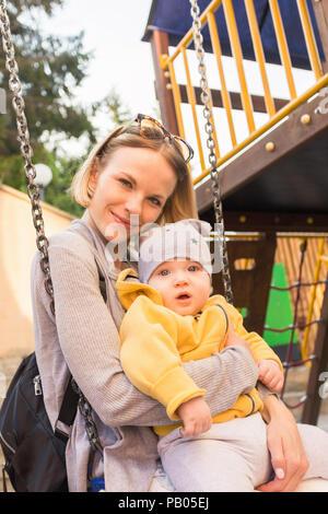 Mutter und Sohn Fahrt auf einer Schaukel auf dem Spielplatz - Stockfoto