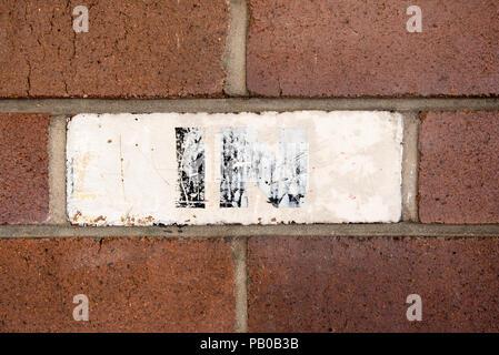 Eine blasse Hand in Zeichen mit schwarzen Buchstaben auf weißem Hintergrund über ein Gesicht Backstein auf eine Wand bemalt bemalt - Stockfoto