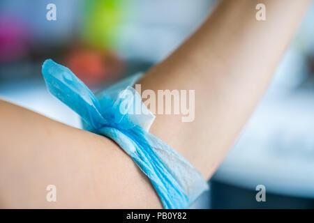 Blau Mullbinde auf weibliche Arm nach einer Blutspende. - Stockfoto