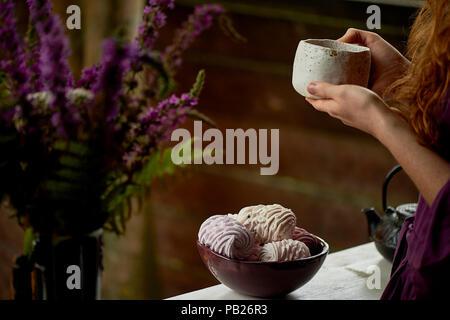 Rothaarige Mädchen in einem lila Kleid mit einem massiven Ton Tasse mit Tee. Tee auf die frische Luft. Genießen Sie das Leben - Stockfoto