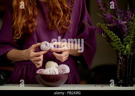 Rothaarige Mädchen in einem lila Kleid bricht ein Stück Marshmallow. Weiter ist eine Schüssel mit Dessert und eine Vase - Stockfoto