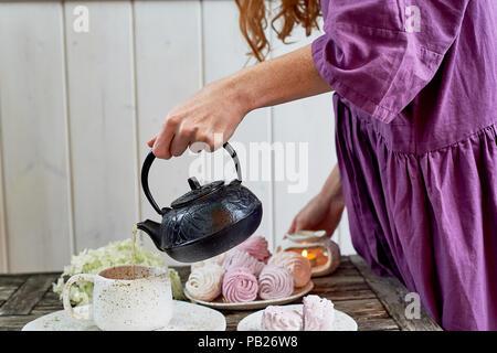 Das rothaarige Mädchen in ein lila Kleid gießt Kaffee in eine Tasse, die Tabelle in die Luft gesetzt ist. Marshmallow. - Stockfoto