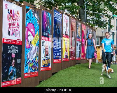 Edinburgh Festival 2018 in George Square, Edinburgh, Schottland, Großbritannien, 26. Juli 2018. Ein Paar mit einem Spaniel hund geben Sie den George Square, die mit Fringe Festival Poster einschließlich Andrew Lawrence ausgerichtet ist und aus der blauen Sänger - Stockfoto