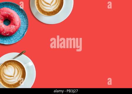 Ansicht von oben. Zwei Tassen duftenden Kaffee Cappuccino und eine Reihe von donut auf einem roten Hintergrund. In der Nähe Platz für Text. Stockfoto