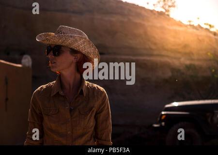 Schöne junge Frau im Land mit goldener Hintergrundbeleuchtung von Sonnenuntergang im Hintergrund. leben verschiedene für Happy lifestyle Konzept. - Stockfoto