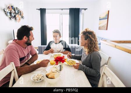 Glücklich und freundlich kaukasischen Familie gemeinsamen Mittagessen zu Hause. weiße Wand und ein helles Bild. Genießen Sie gemeinsam den Tag lächelnd und mit Liebe ein - Stockfoto
