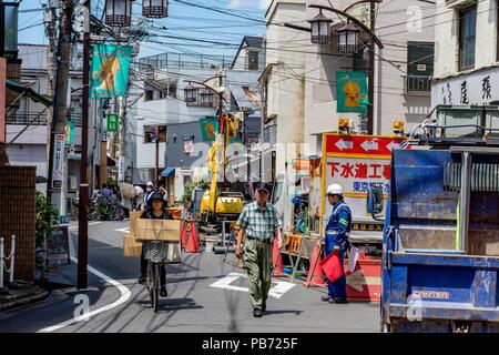 Frau auf Fahrrad mit großen Boxen Zyklen vorbei an alten Menschen vorbeigehen Straße Baustelle mit Hut mit roten Fahnen, in Tokio, Japan. - Stockfoto