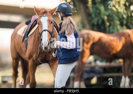 Junge hübsche Mädchen, das Pferd für die Fahrt vorbereiten - Stockfoto