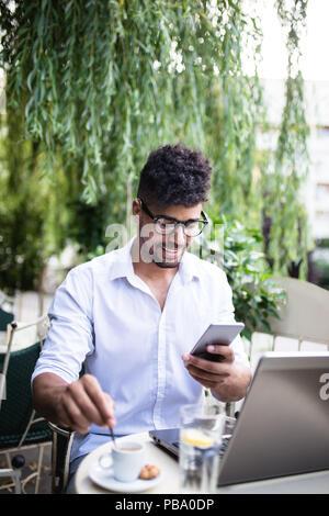 Junge attraktive afro-amerikanische Geschäftsmann sitzt im Cafe Bar, Kaffee trinken und dabei einige Arbeiten am Laptop. - Stockfoto
